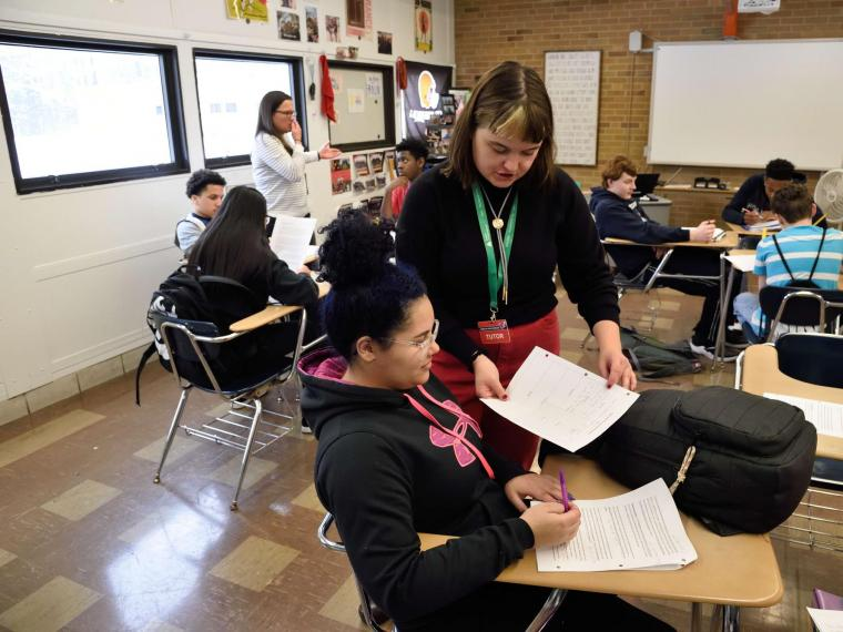 writing tutor assisting high school student