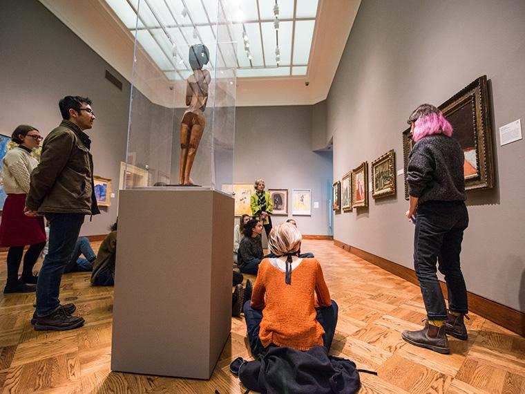 students stand in Allen Memorial Art Museum gallery during the Practicum in Museum Education class.