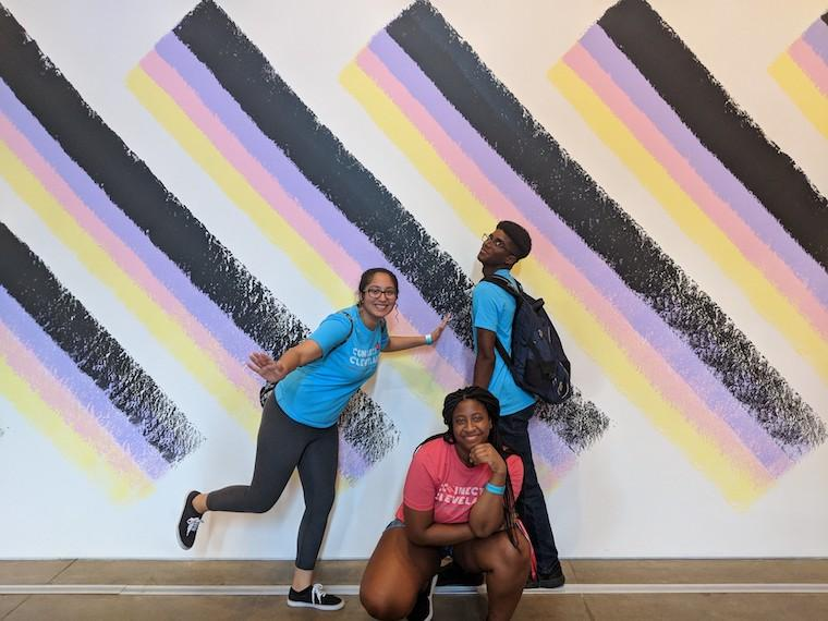 Students pose in front of museum artwork.