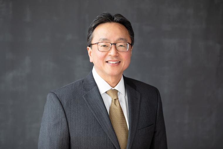 David Kamitsuka smiling with glasses gray suit coat and tan tie.