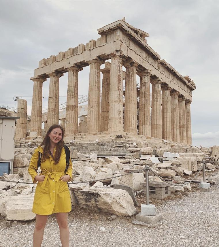 Woman standing in front of ancient stone building.