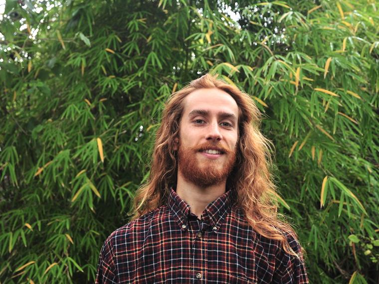 young man with long red hair wearing plaid shirt while standing under green trees.