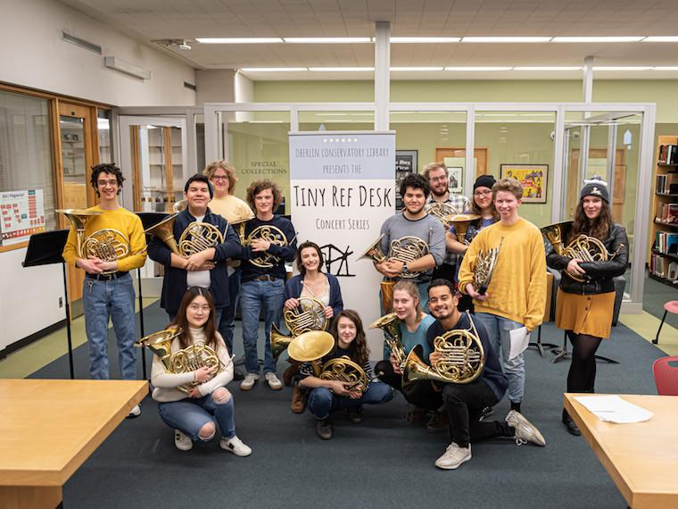 Students with French horns pose in front of a sign.