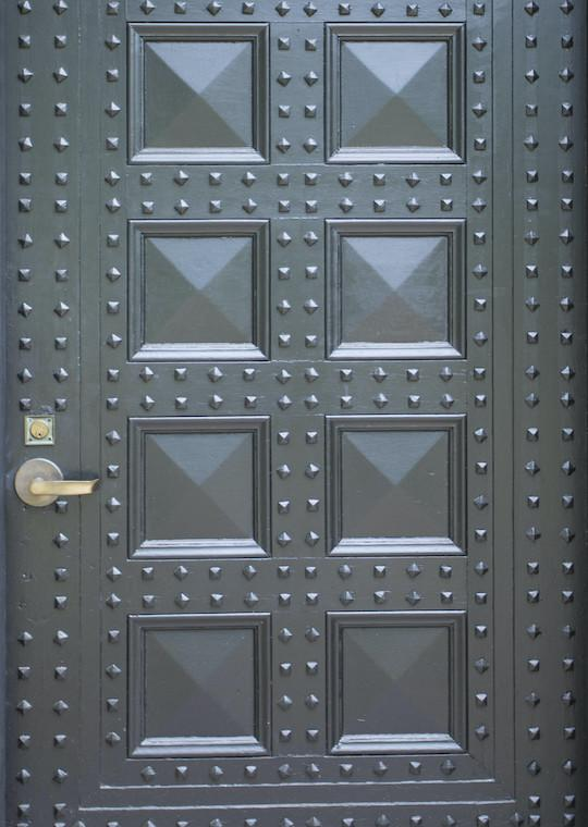 Eight panel door with square nail heads.