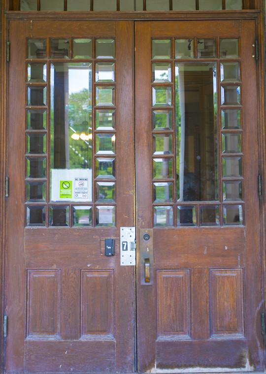 Double wooden doors with glass squares surrounding large glass panes