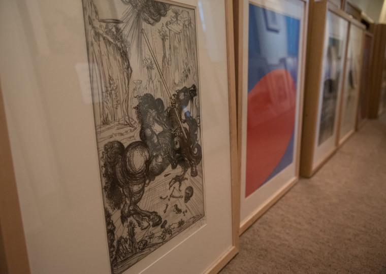 A row of prints and paintings on a floor.