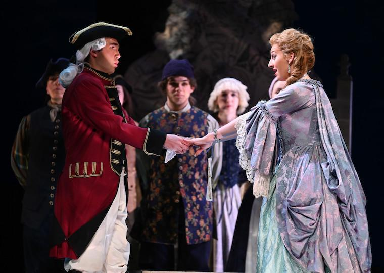 Two actors dressed in 18th century costume hold hands on stage.