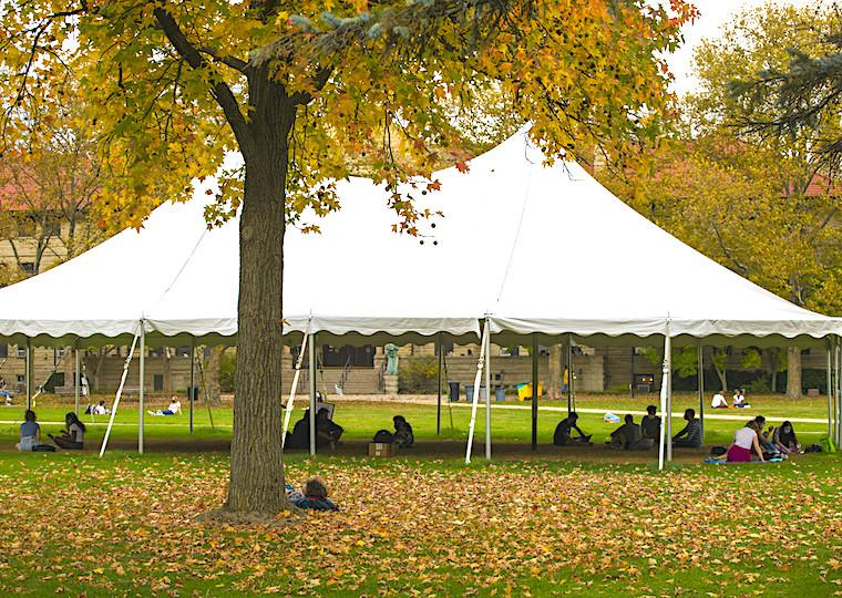 A large tent with people in it on a fall day.