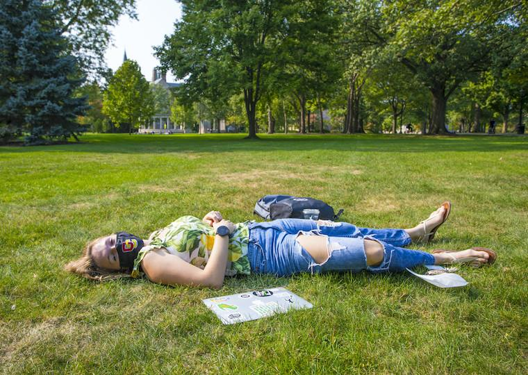 A girl laying in the grass in the park.