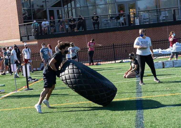 a student flips a large truck tire.