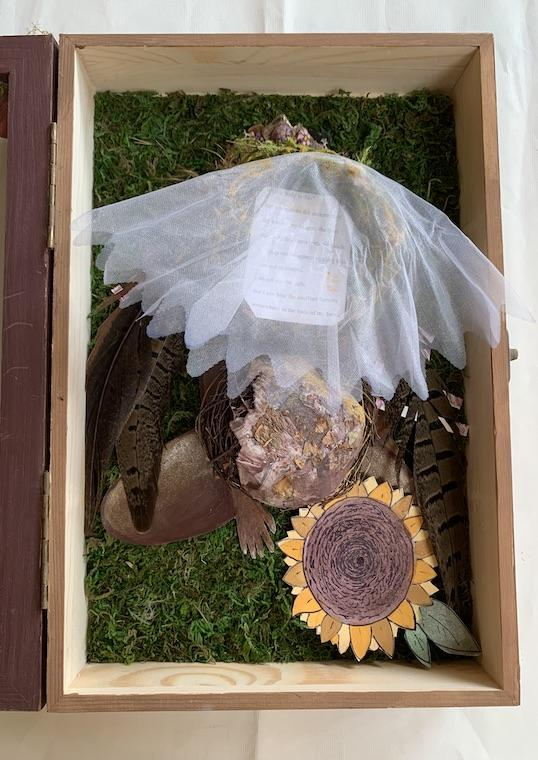A box filled with netting and a paper sunflower