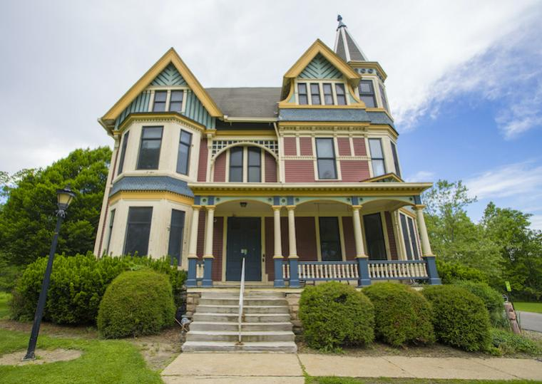 A Victorian style home with wooden porch and stone steps