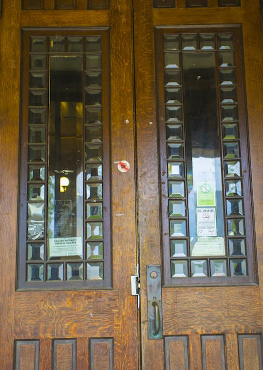 A set of slender wooden doors surrounded by tall insets of glass