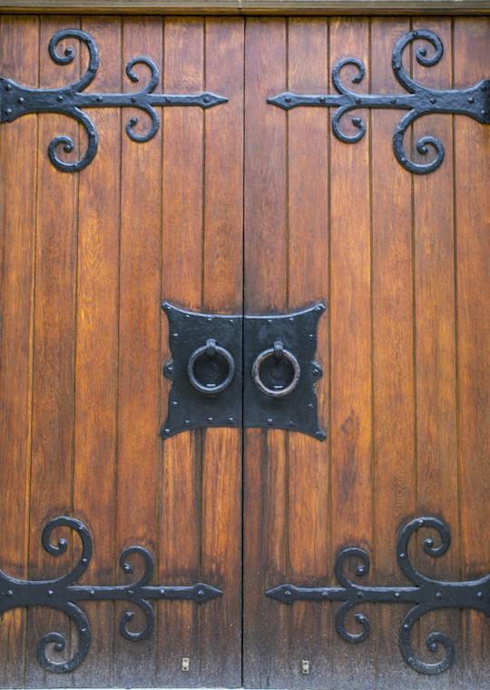 Double wooden heavy doors with round metal handles.