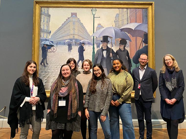 Group of students standing in front of 'Paris Street; Rainy Day' by Gustave Caillebotte.