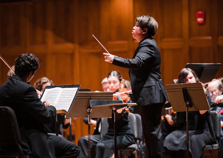 A woman conducts an orchestra.