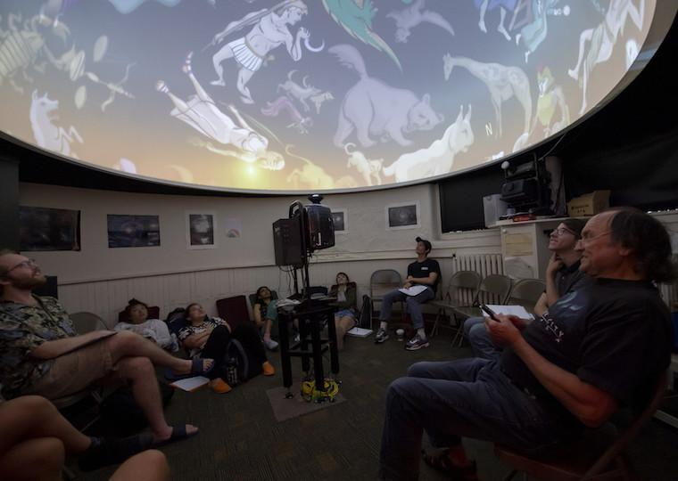 Students look at a astrological symbols in an astronomy class.