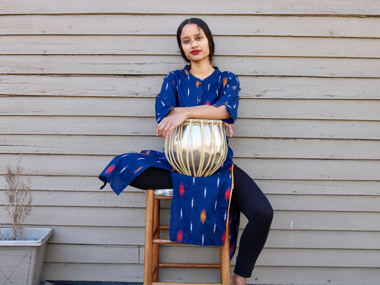 woman in blue dress sits on stool with drum.