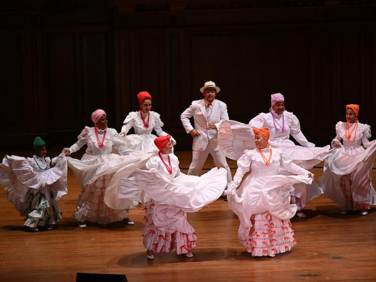 Seven women dance in full skirts and a man dances with them on stage.