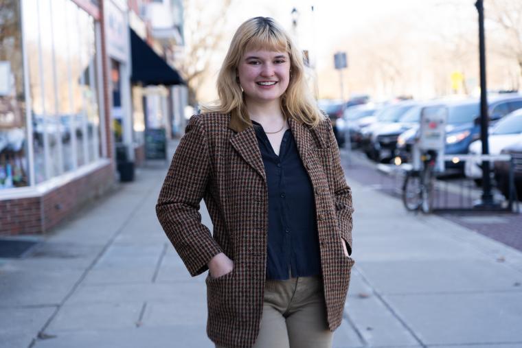 Blond woman standing in tweed jacket standing on street sidewalk.