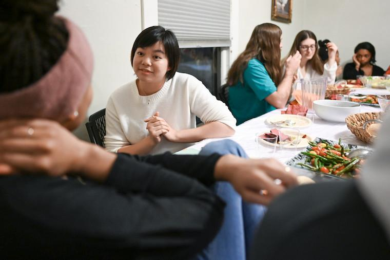 Six students sitting at a table set with food.