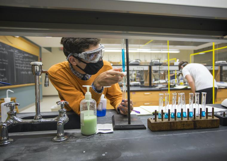 A student looks at a long cylinder with colored liquid in it.