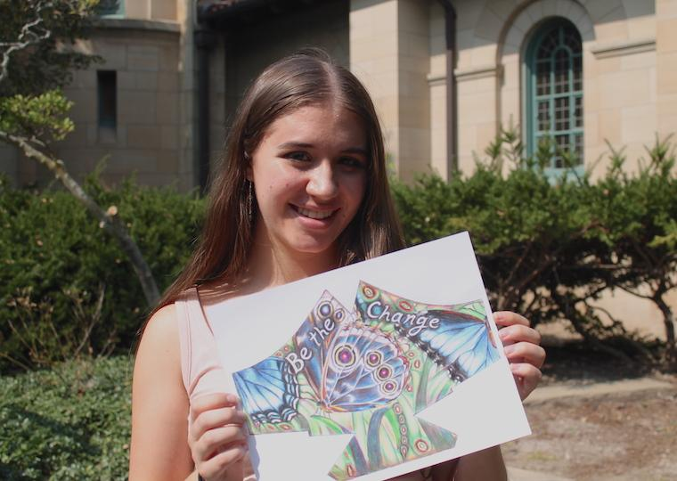 A girl holds a drawing of a mask.