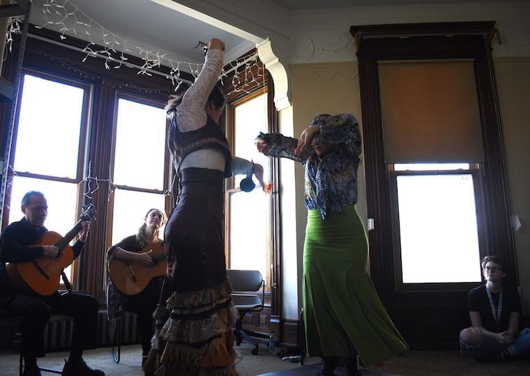 Two women dance in front of a window.