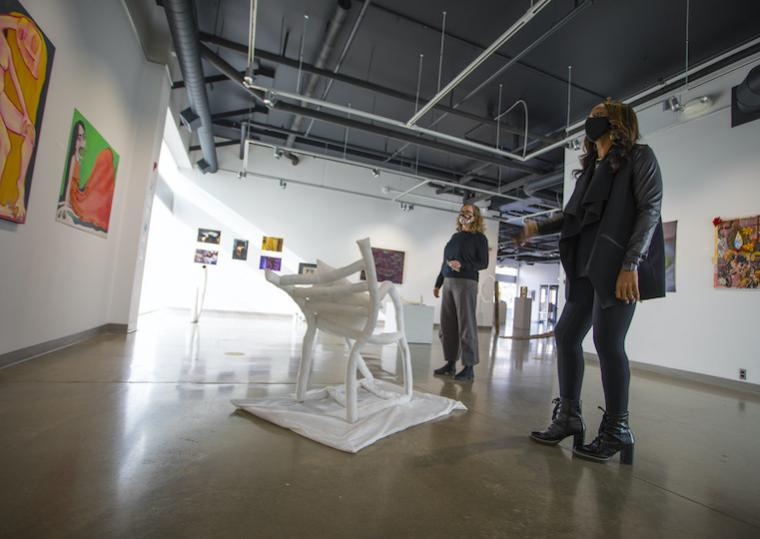 Two women stand in the middle of an art exhibit.