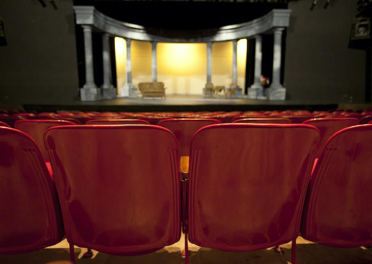 An empty auditorium facing a stage with columns on it.
