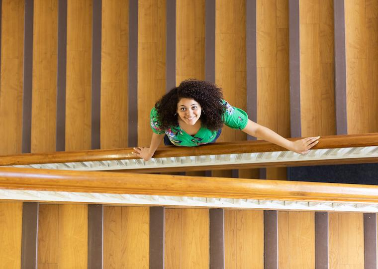A girl looks up while standing on a wooden staircase.