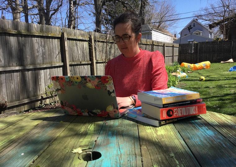 A woman types on a laptop in her backyard.