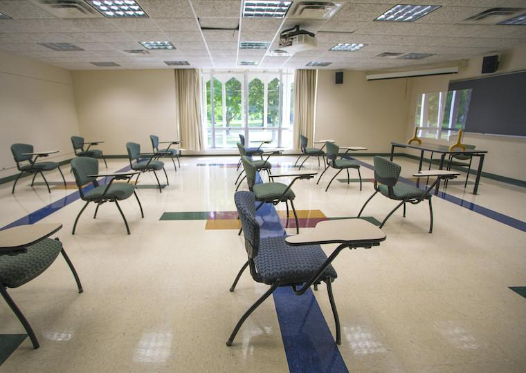 A classroom with desks facing toward a chalkboard.