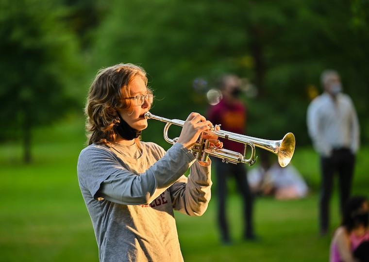A student plays a trumpet in a park.