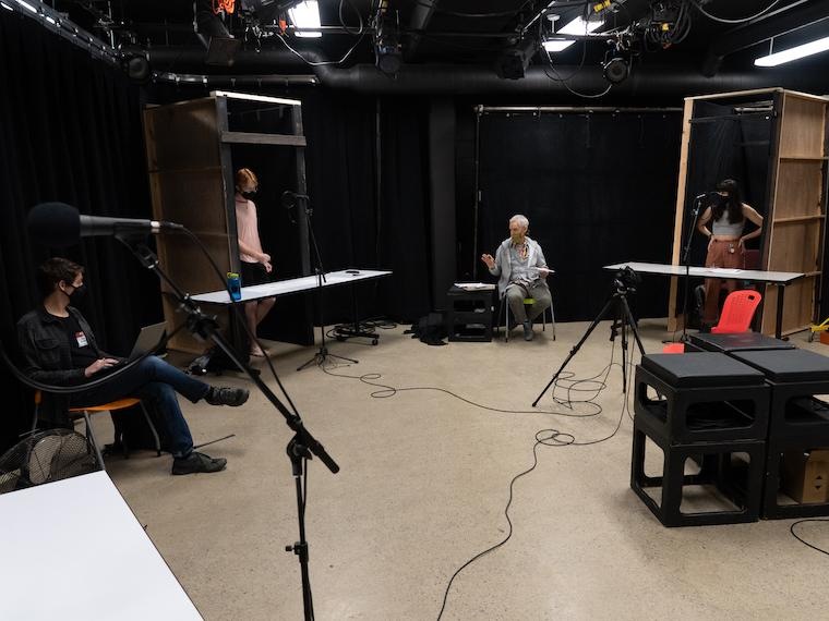 four pepple spread out in a room making an audio recording.