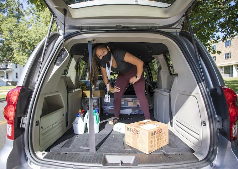 A girl wearing a face mask crouches inside the back of an open car trunk.