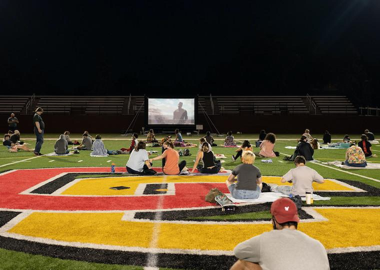 Students sit on a football field and watch a movie on a large screen.