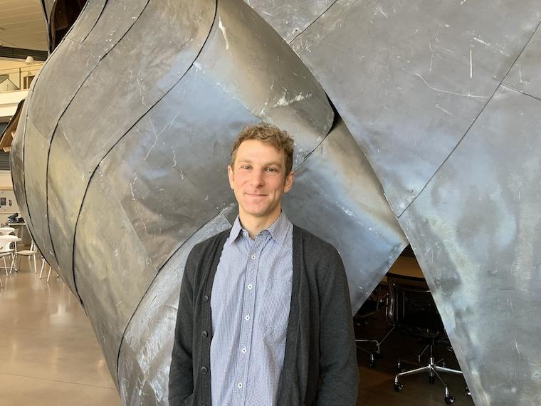 Young man in blue denim shirt nd dark gray sweater standing in front of metal sculpture.