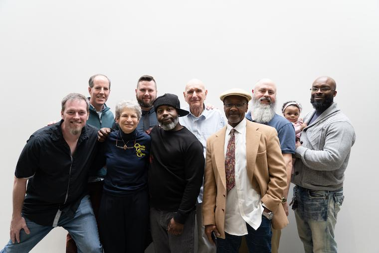 Eight white and black men of all ages, one woman, and a man holding a baby post for photo.