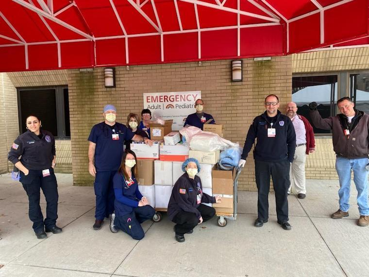 People receive cart of donations outside emergency room.