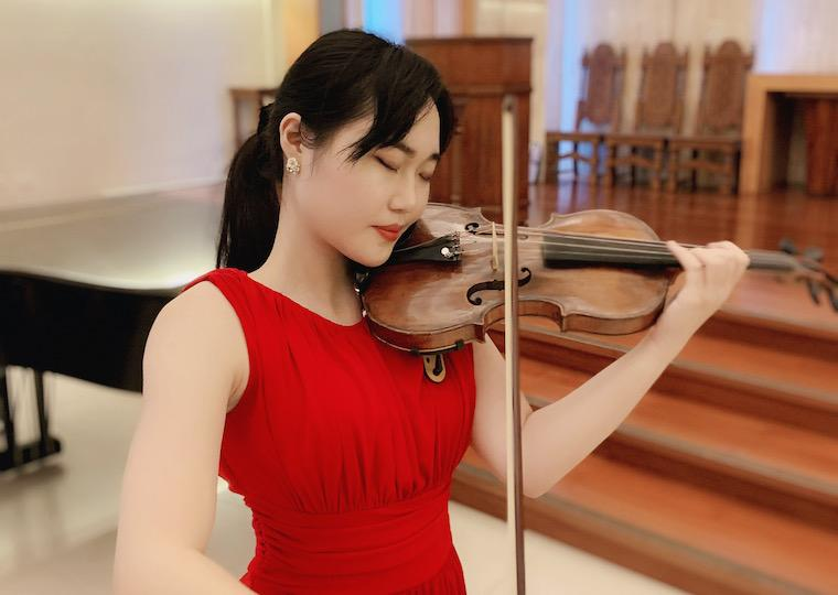 Asian girl in red dress plays a violin.