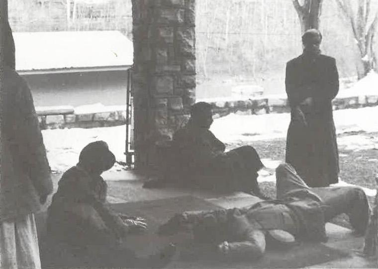 Three students lay on a concrete porch with two other students standing nearby.