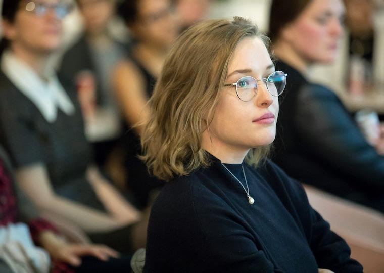 A girl wearing glasses sitting in an audience.