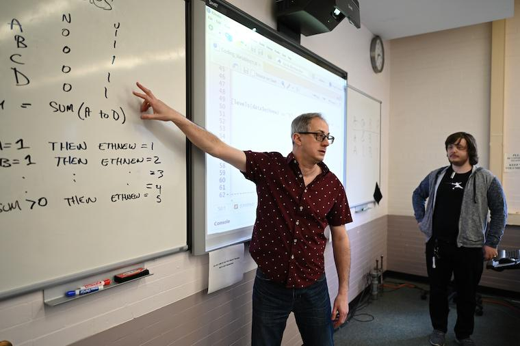 Man pointing at white board while a student looks on.