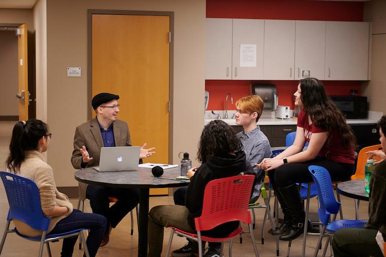 Four students and professor talk while seated at a round table.