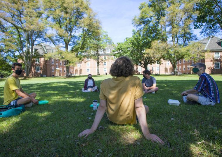 Students sit in a circle on a lawn.