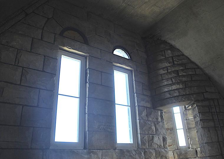 A stone wall with two windows and a long window on a circular wall.