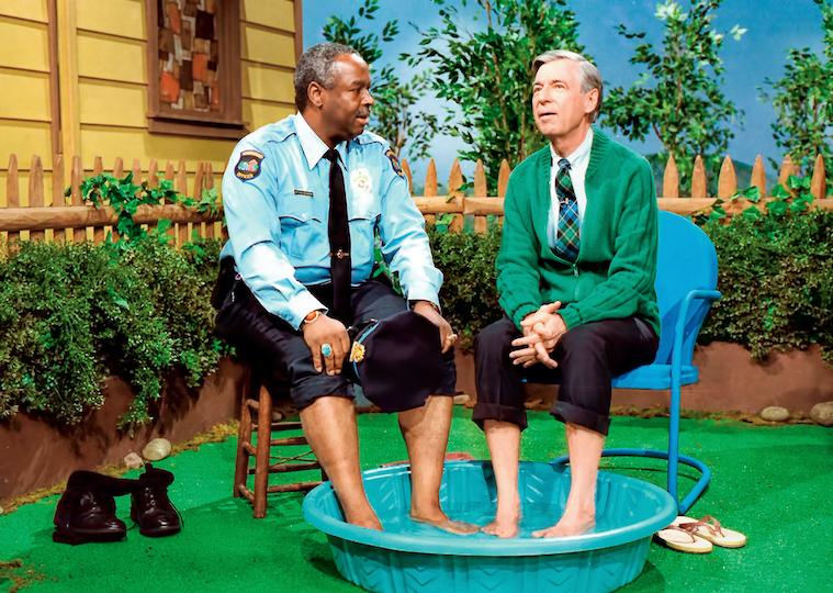 Two men sit with their feet in a child's pool.