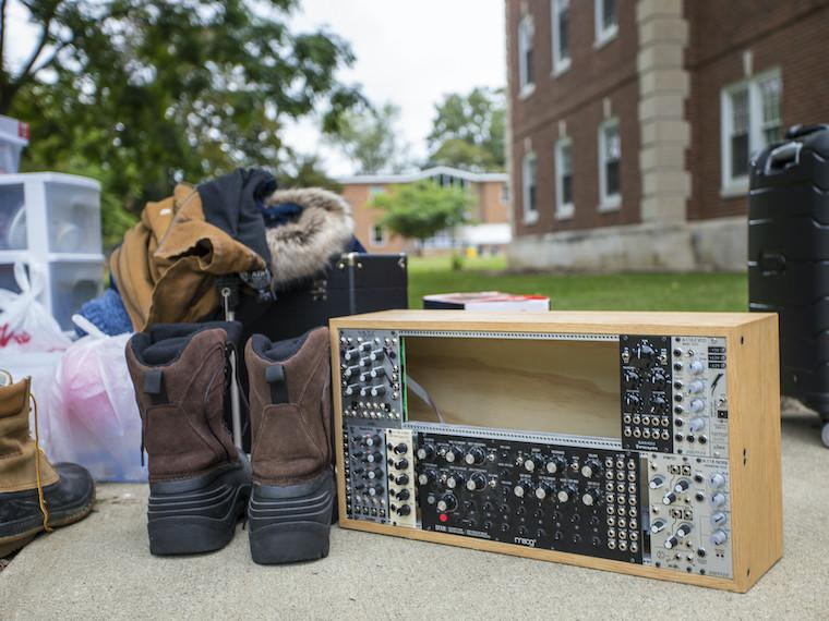 A pair of boots and a soundboard sit on a sidewalk.
