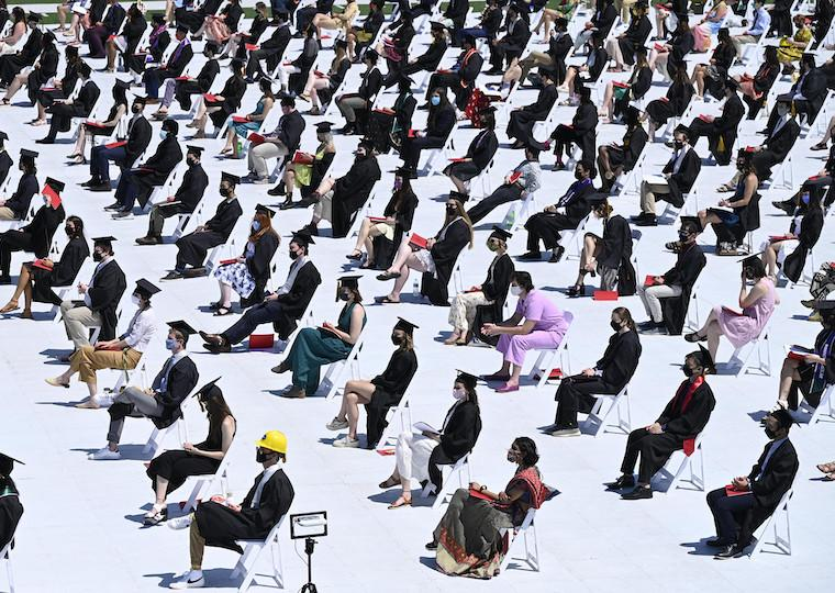 Alarge number od graduates sit 5 feet apart in a football field.